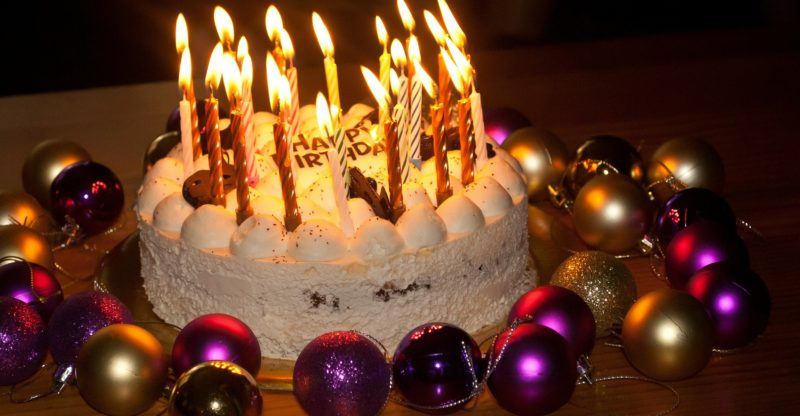 Birthday cake and lots of fired candles on top of it and beside the cake are Christmas balls