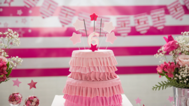 Multi-tiered pink cake decorated in fondant that looks like skirts